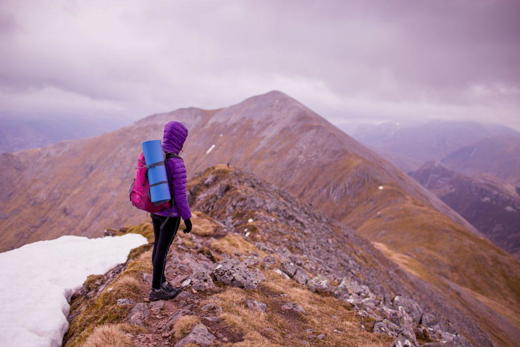 Cartão Nubank: imagem ostra uma pessoa de casaco roxo em cima de uma montanha, com um pouco de gelo ao lado