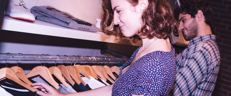 Mulher jovem olha arara de roupas, dentro de uma loja de vestimentas.