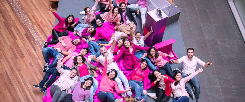 Foto aérea de grupo de pessoas vestindo rosa, sentados em uma arquibancada roxa