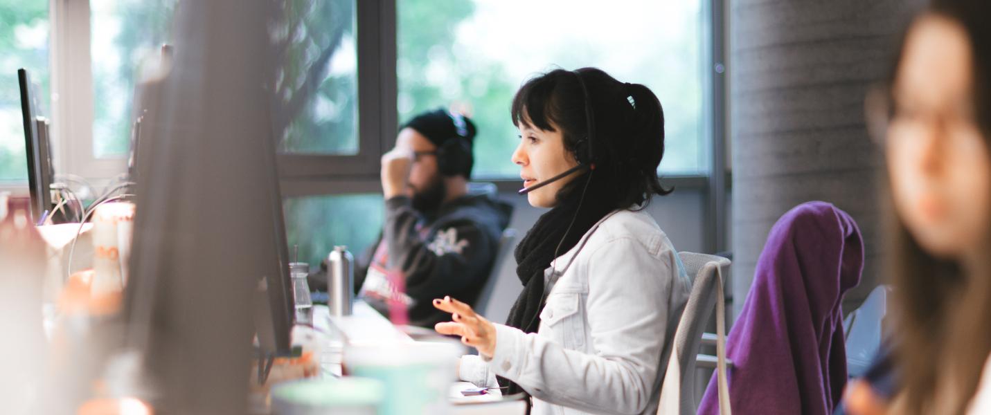 Três pessoas trabalhando no escritório do Nubank. O foco da foto está em uma mulher, jovem, atendendo clientes com um headphone