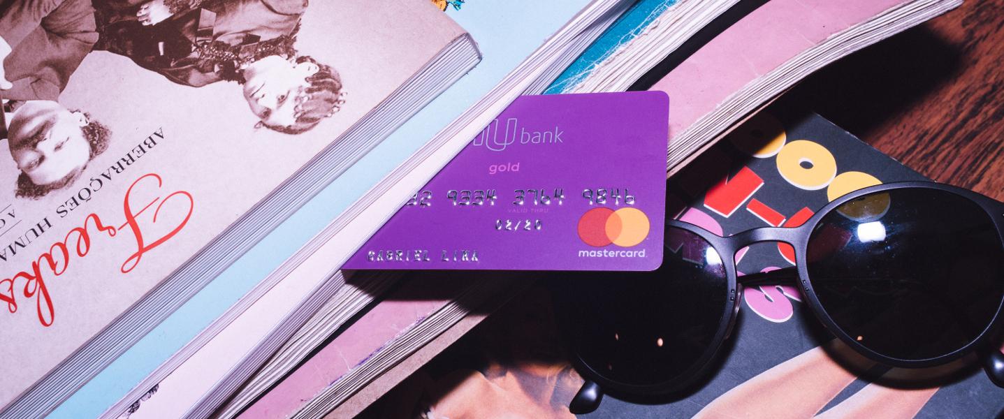 Cartão de crédito Nubank em meio a livros e revistas
