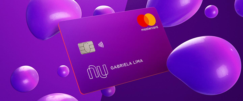 Novo cartão Nubank (com roxo metalizado) flutuando em um fundo de bexigas roxas