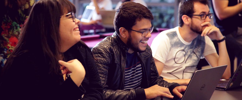 três pessoas (coincidentemente todas de óculos!), sentadas em uma mesa sorrindo. Uma delas está mexendo no computador
