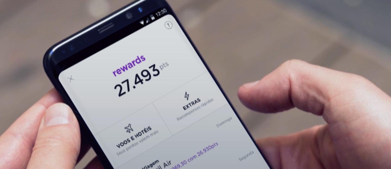 Duas mão seguram um celular. A tela mostra os pontos acumulados na interface do Nubank Rewards no aplicativo do Nubank