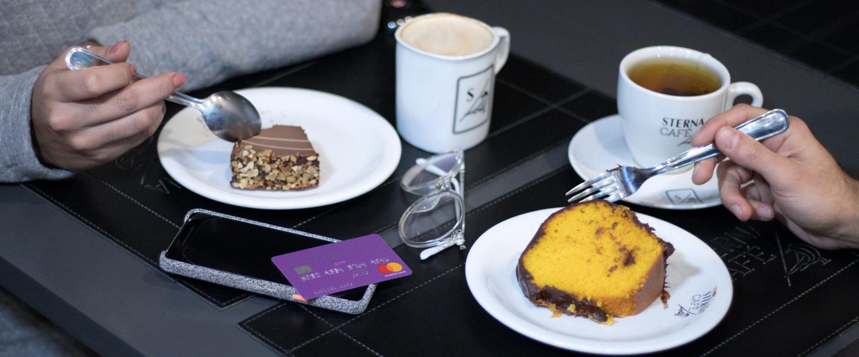 Duas pessoas comendo bolo e tomando um café, com o cartão exposta na mesa.