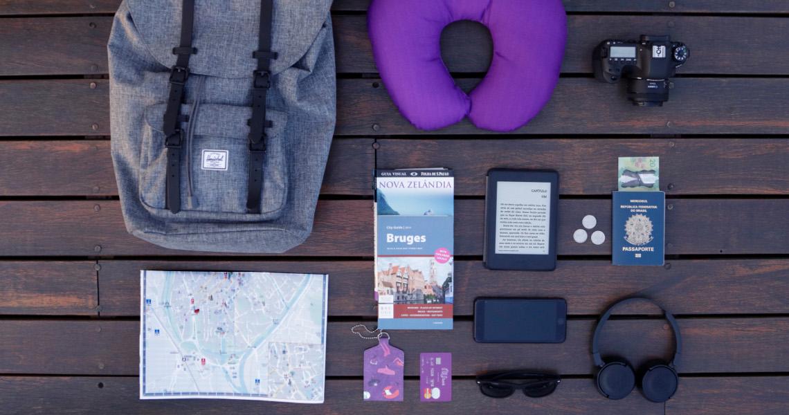 Diversos itens de viagem vistos de cima: mochila, mapa, almofada de pescoço, máquina fotográfica, passaporte e cartão Nubank