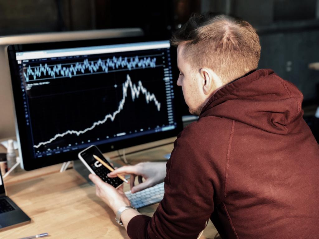 Homem loiro sentado, de costas, mexendo no celular e em frente à uma tela de computador com um gráfico de linhas mostrando a flutuação de algum valor