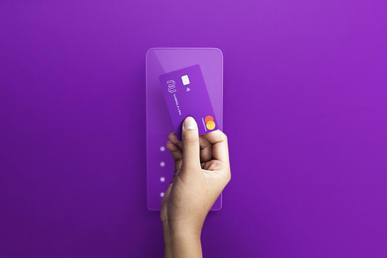 Mão segurando o cartão Nubank roxinho passa ele por cima de uma maquininha de pagamentos - também roxa. O fundo da foto é (adivinhem) roxo também!