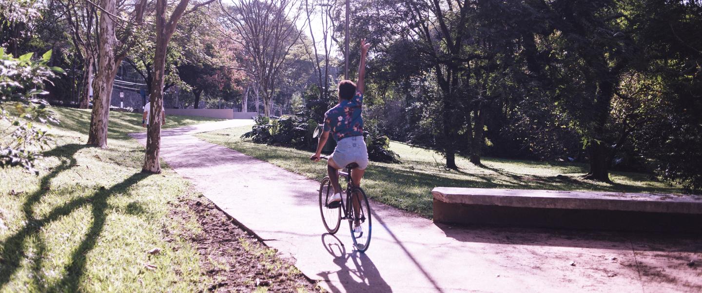 Jovem, de costas, andando de bicicleta com uma das mãos para cima. O dia está ensolarado e a bicicleta está em um parque com árvores