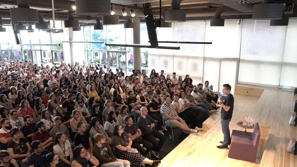 O auditório do Nubank, com mais de 300 pessoas sentadas, e o CEO David Velez falando no palco