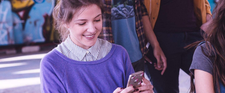 Solicitar cartão de crédito pela internet: uma garota sentada usando suéter roxo usando um celular