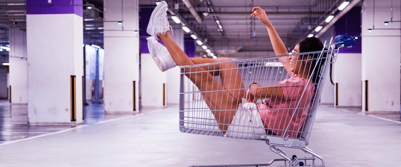 Jovem sentada dentro de um carrinho de supermercado, de shorts tênis e camiseta, com as pernas para cima. Ela está levantando um braço para o alto e sorrindo. O carrinho está em um grande estacionamento vazio.