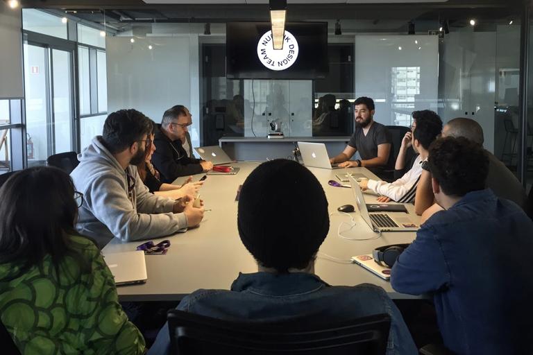 Sala de reunião com grupo de pessoas reunidas em torno de uma mesa comprida. Uma TV, pendurada no teto, mostra o símbolo do Design no Nubank