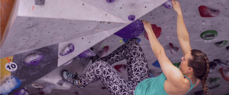 Mulher escalando uma parede de escalada interna
