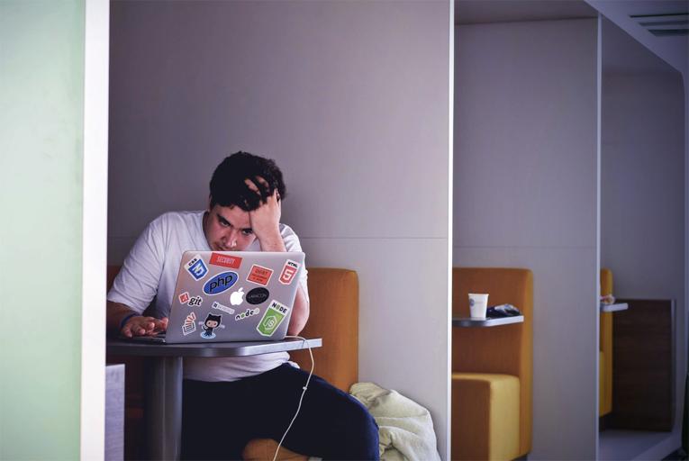 Rapaz sentado em uma mesa, olhando para um computador cheio de adesivos, com a mão na cabeça e cara de preocupado