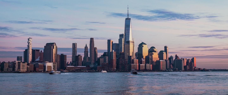 Horizonte com os prédios da ilha de Manhattan, o mar e o céu arroxeado do entardecer