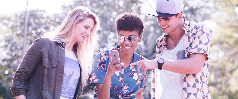 Três pessoas, duas mocas e um rapaz, de pé, olhando para o telefone na mão da jovem do meio.