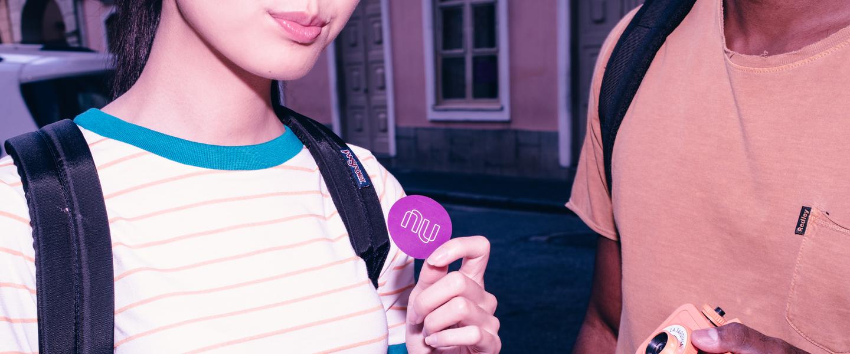NuConta: Mulher de blusa listrada segurando adesivo do Nubank.