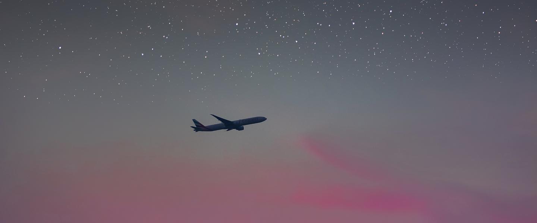 A foto mostra um avisão voando em um céu ao anoitecer. O céu está rosa na linha do horizonte e cheio de estrelas mais acima