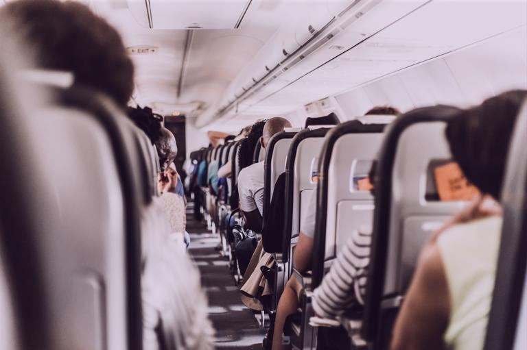 Foto mostra corredor de avião com cadeias ocupadas vistas de costas
