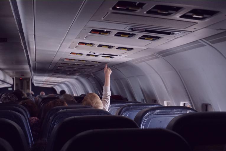 A foto mostra o interior de uma aeronave comercial. De costas, uma criança estica o dedo e tenta alcançar as luzes sobre a sua poltrona