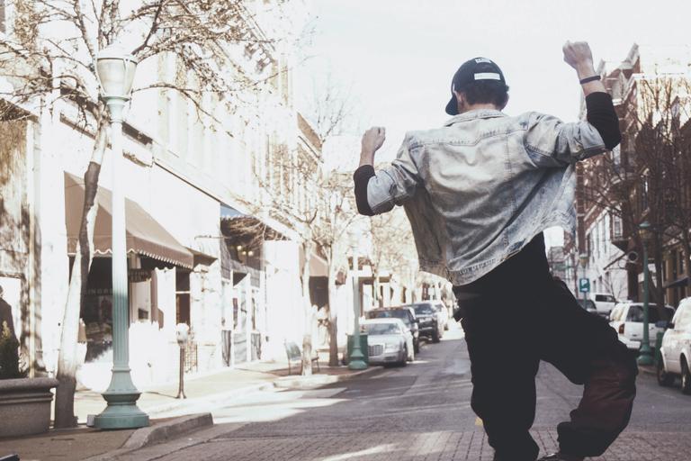 Jovem de bone, jaqueta jeans e calça preta visto de costas pulando no meio da rua com os braços para cima