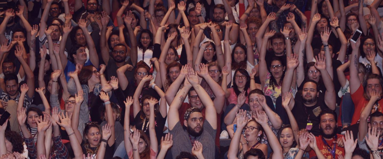 grupo de pessoas em um auditório lotado, todas com as mãos para cima