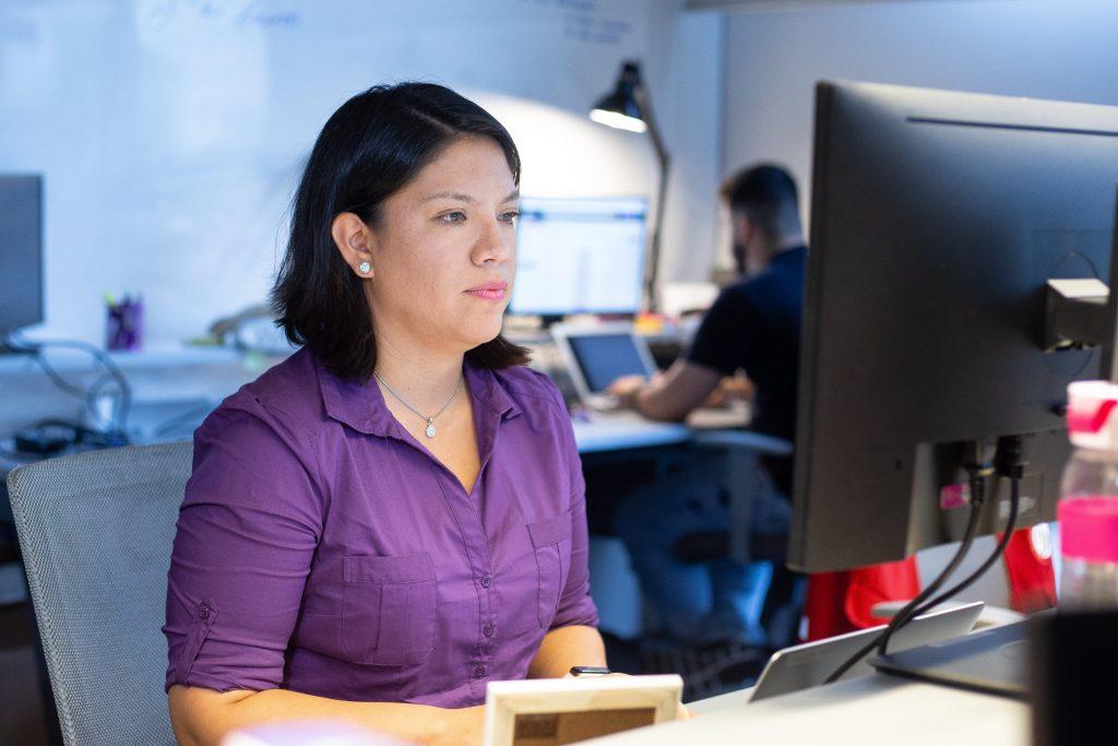 Foto mostra Cecilia Gutierrez sentada em frente a um computador. Ela está usando uma camisa roxa.