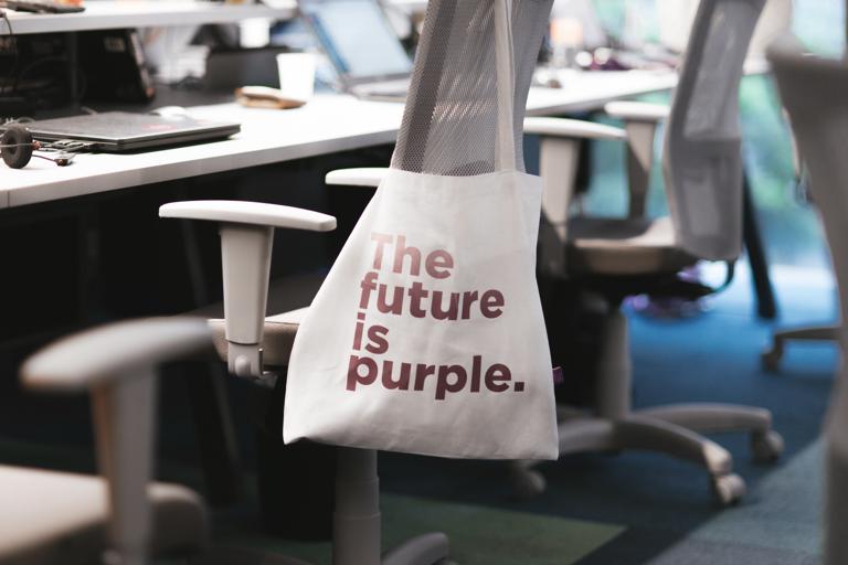 """Foto mostra uma sacola branca com a estampa """"The Future is Purple""""(o Futuro é Roxo, em Português) pendurada em uma mesa"""