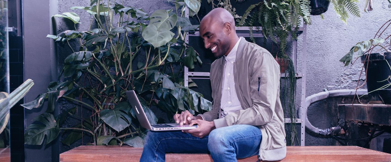 Rapaz sentado em um banco de madeira, vestindo jeans e uma jaqueta de sarja, sorrindo ao olhar para um notebook no seu colo