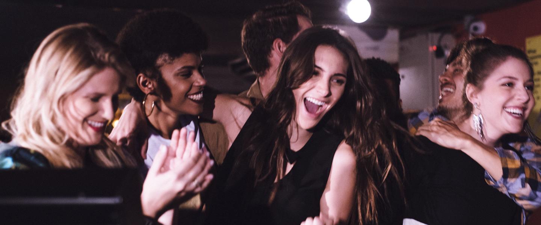 Grupo de amigos abraçados em uma festa, sorrindo