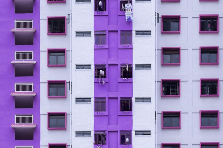 Imagem mostra a fachada de um prédio com muitas janelas. A faixa central do prédio e as laterais são roxas. Os beirais das demais janelas são rosa escuro