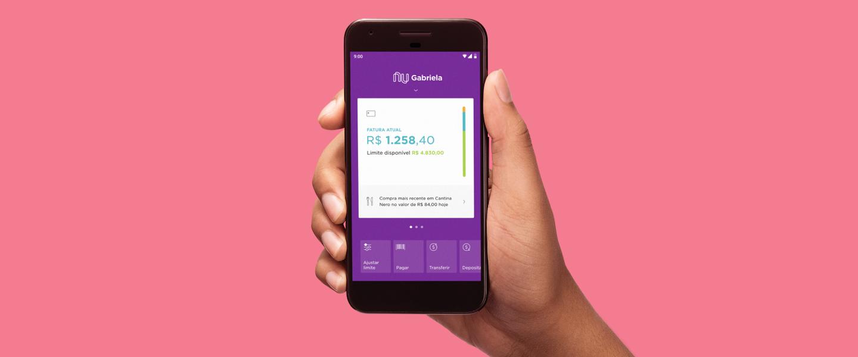 Fundo rosa coral e a foto de uma mão segurando um telefone. Nele, a imagem do aplicativo do Nubank aberto na tela que mostra a fatura aberta do cliente