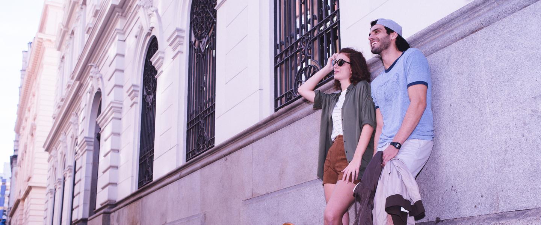 Uma jovem e um jovem encostados em uma parede de prédio antigo, olhando para o horizonte e sorrindo. Ela veste um shot marrom, óculos de sol e blusa cinza, e ele camiseta e boné azuis.