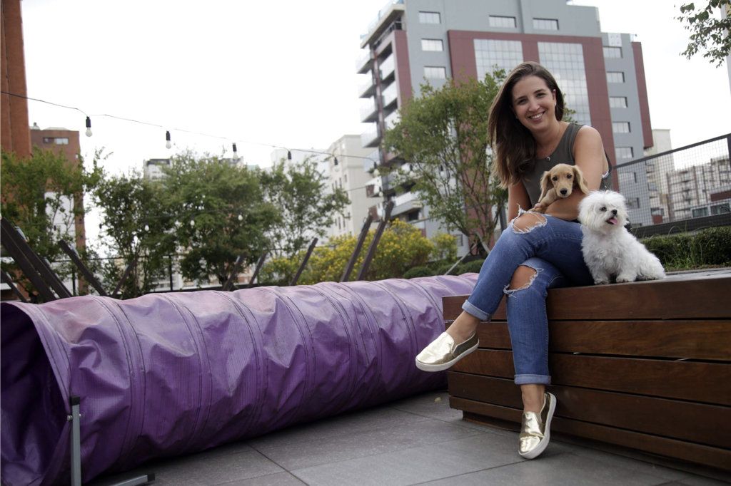Jovem sentada em um terraço com dois cachorros ao seu lado