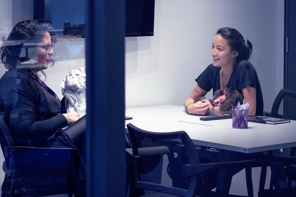 Duas mulheres em uma sala de reunião, com portas de vidro. Cada uma delas está com um cachorro no colo