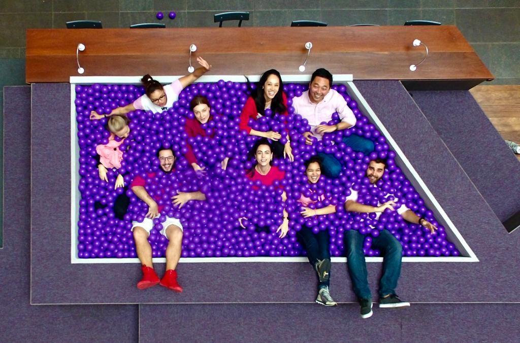 Vista de cima da piscina de bolinhas roxas do Nubank, com funcionários dentro, olhando para a foto e sorrindo