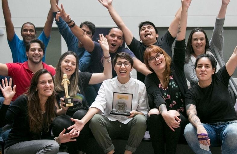 Xpeers sentados segurando os prêmios que o Nubank recebeu por atendimento ao cliente.