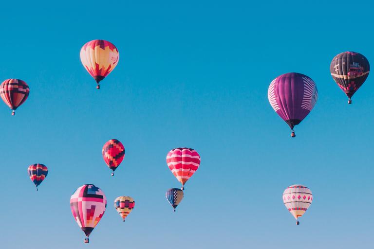 Balões de diversas cores e tamanhos voando em um céu azul.
