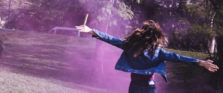 Jovem de costas, correndo e pulando, com os braços aberto e passando em meio à uma fumaça roxa