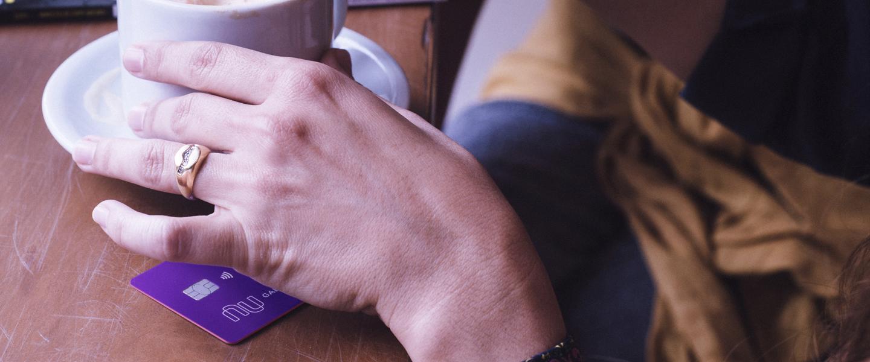 Mesa com uma pessoa mexendo uma xícara de café apoiada sobre cartão de crédito Nubank.