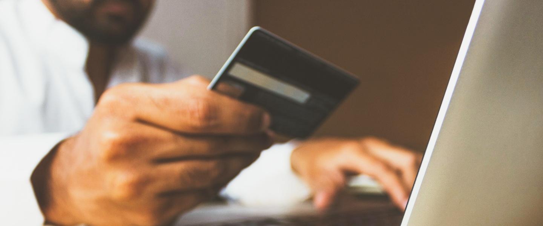 golpes no cartão de crédito: homem escreve no notebook ao mesmo tempo em que segura um cartão de crédito azul
