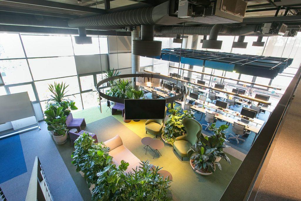 Andar do Nubank, com mesas de trabalho compartilhadas, plantas e sofás.