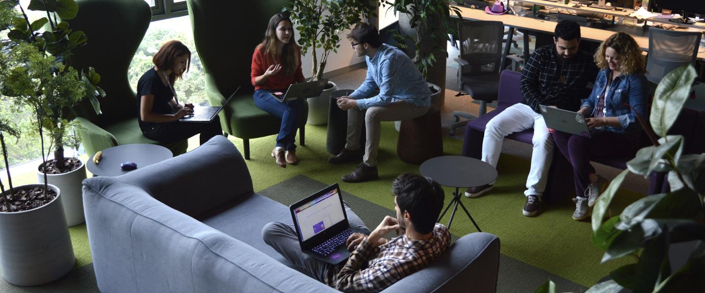 Pessoas sentadas em poltronas e sofás, conversando, em uma área do escritório do Nubank repleta de plantas