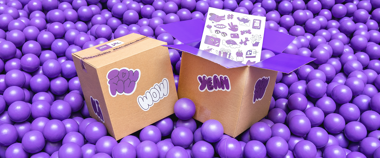 Duas caixas com adesivos roxos e criativos na piscina de bolinhas roxas.
