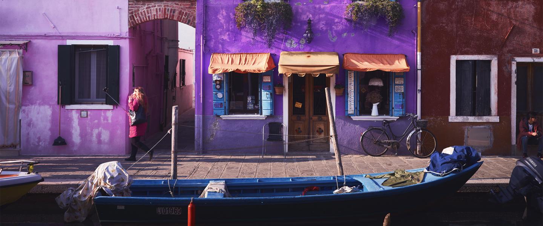 Casinhas roxas em frente à um canal com um barco