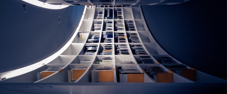 Imagem é uma brincadeira com uma biblioteca de livros. A foto é uma instante na horizontal, curva, com livros.