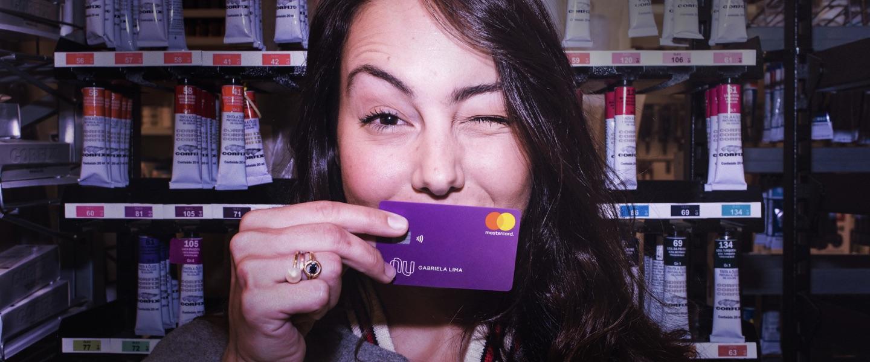 NPS Nubank: Jovem piscando com um cartão Nubank em frente à sua boca