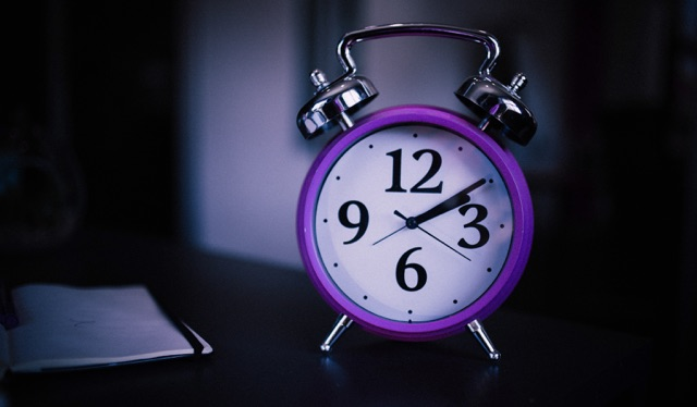Relógio de ponteiros branco, com a borda roxa