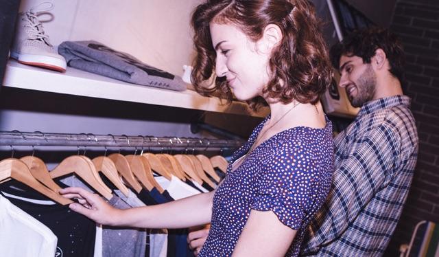 Uma jovem de vestido roxo e cabelos curtos olha para uma arara de roupas em uma loja. Ao fundo, um rapaz também mexe nas camisetas da arara.